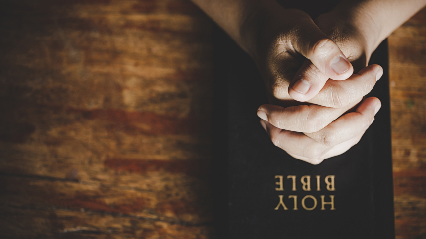 Bible with praying hands